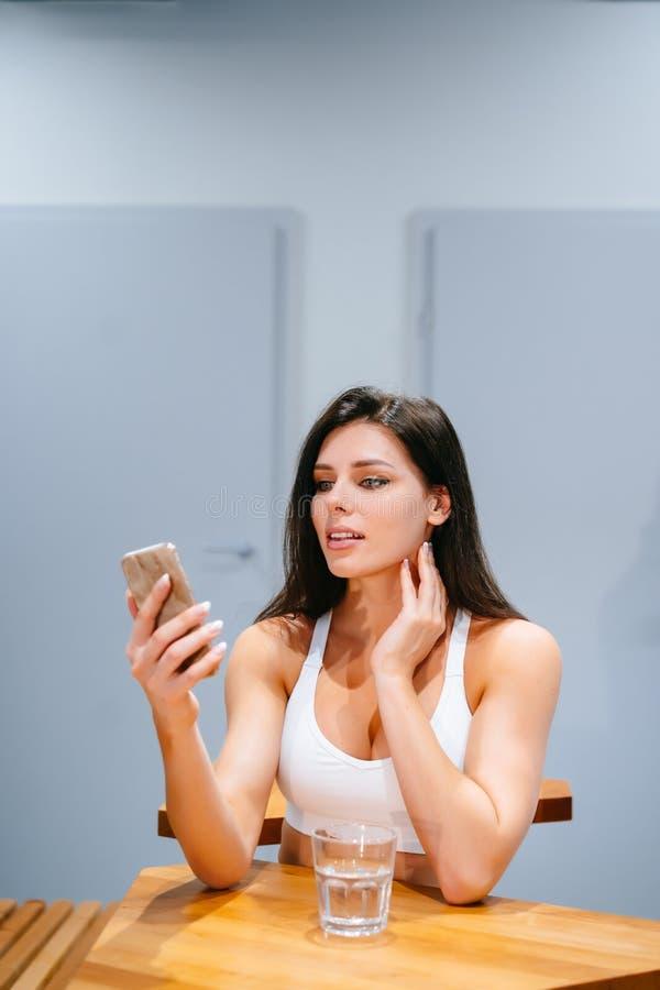 Livsstil för flicka för ung kvinna sittande genom att använda smartphonen efter utbildningsövning royaltyfria bilder