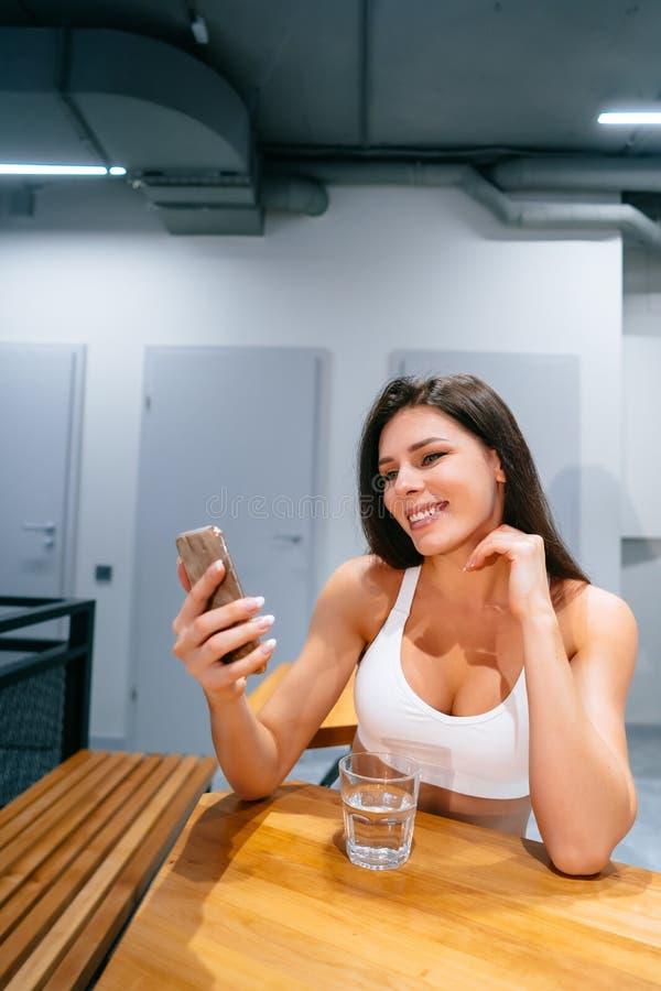 Livsstil för flicka för ung kvinna sittande genom att använda smartphonen efter utbildningsövning royaltyfri fotografi