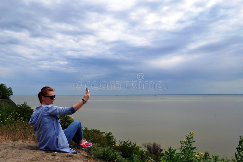 Livsstil, fritid, sommar, teknologi och folkbegrepp - le den unga kvinnan eller den tonårs- flickan i solhatten som tar selfie me arkivfoton