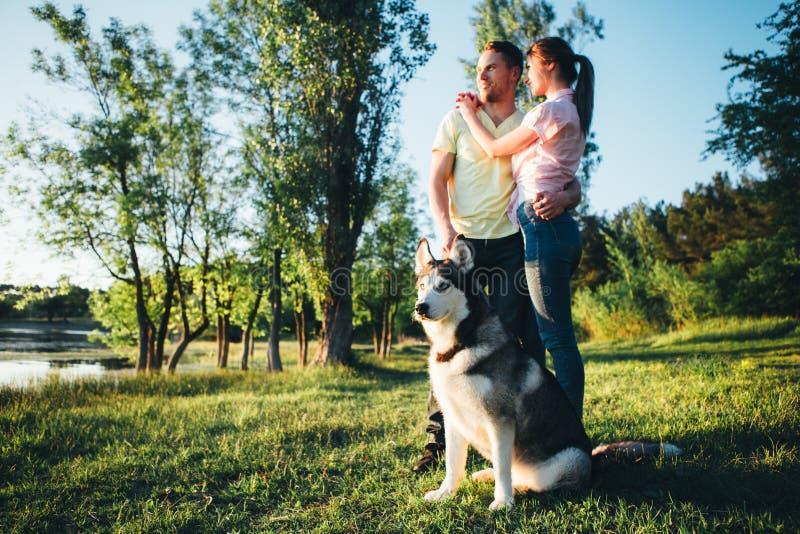 Livsstil lycklig familj av två som vilar på en picknick i parkera med en hund royaltyfri bild