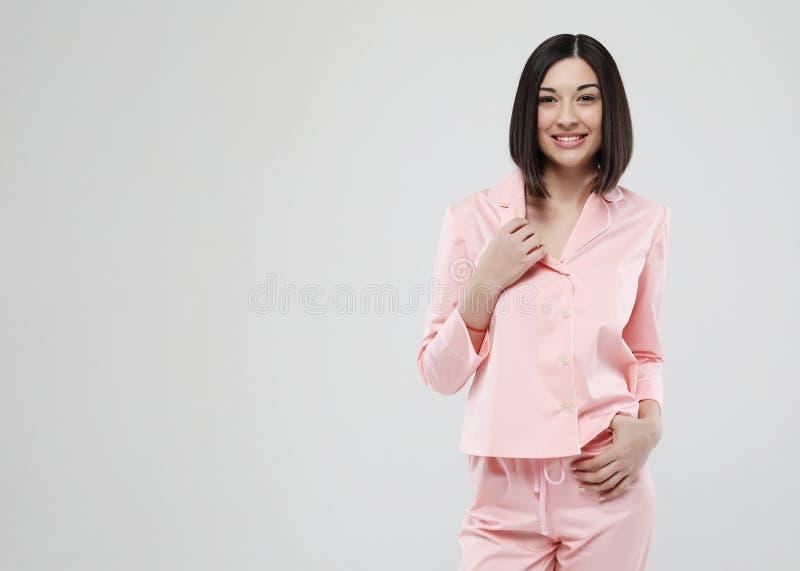Livsstil, mode och folkbegrepp - ikl?dd rosa pyjamas f?r h?rlig brunettflicka ?ver vit bakgrund arkivbilder