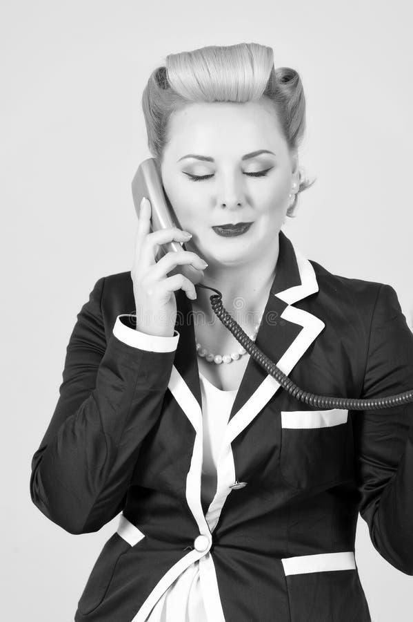 Livsstil och folkbegrepp: den blonda kvinnan talar över telefonmottagaren arkivfoto