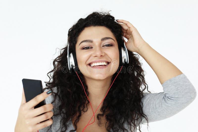 Livsstil och folkbegrepp: Härlig ung kvinna som lyssnar till musik i hörlurar med smartphonen royaltyfri fotografi