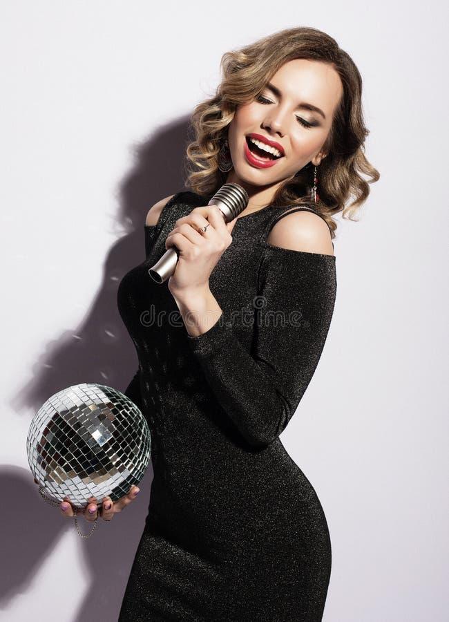 Livsstil och folkbegrepp: kvinna som bär den svarta klänningen, hållande diskoboll och sjunger in i mikrofonen royaltyfri bild