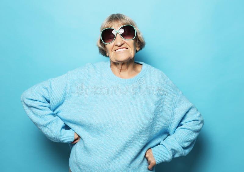 Livsstil och folkbegrepp: Lycklig farmor som bär blått le för tröja royaltyfri fotografi