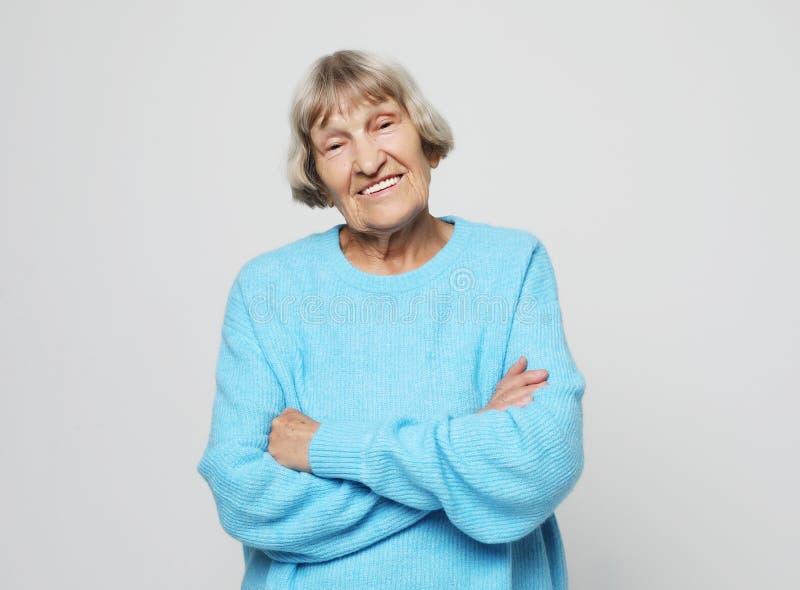 Livsstil och folkbegrepp: Lycklig farmor som bär blått le för tröja royaltyfri bild