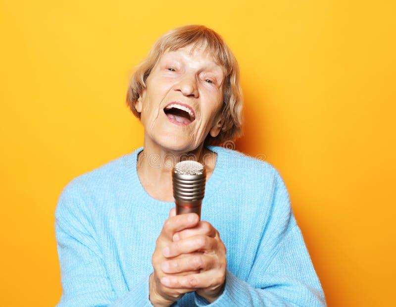 Livsstil och folkbegrepp: Lycklig gammal h?g kvinna som sjunger med mikrofonen och att ha gyckel som uttrycker musikalisk talang royaltyfria bilder