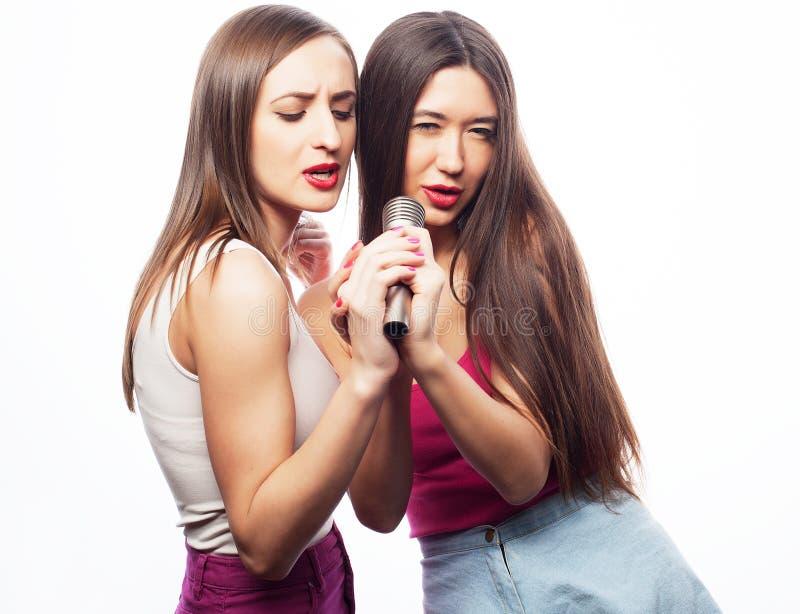 Livsstil och folkbegrepp: Lyckliga flickavänner med mikrofonen över vit bakgrund arkivbild