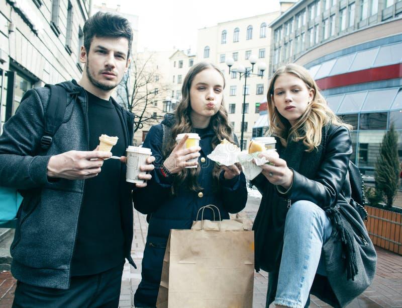 Livsstil och folkbegrepp: två flickor och grabb som äter snabbmat på stadsgatan som har tillsammans gyckel som dricker kaffe royaltyfria foton