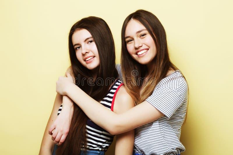 Livsstil och folkbegrepp: Två ung flickavänner som står till arkivfoto