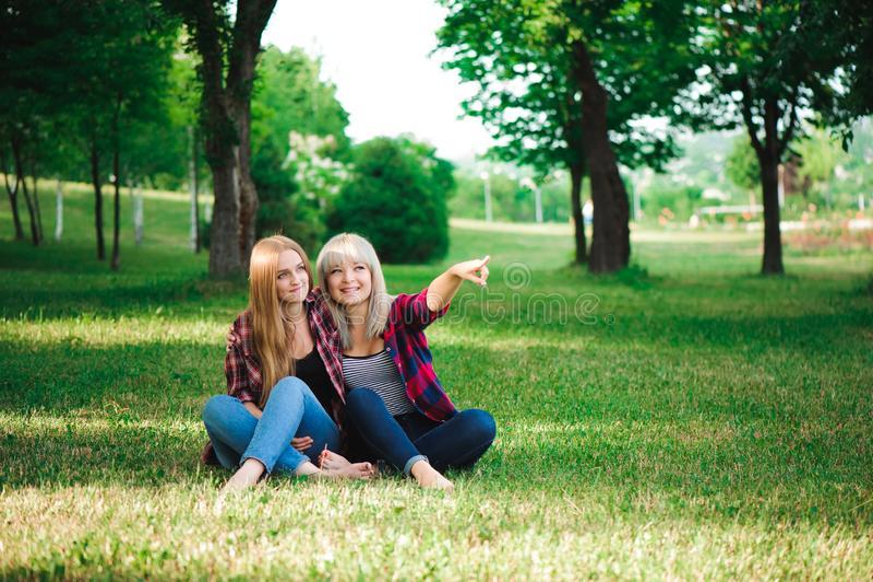 Livsstil och folkbegrepp: Två ung flickavänner som tillsammans sitter och har gyckel arkivbild