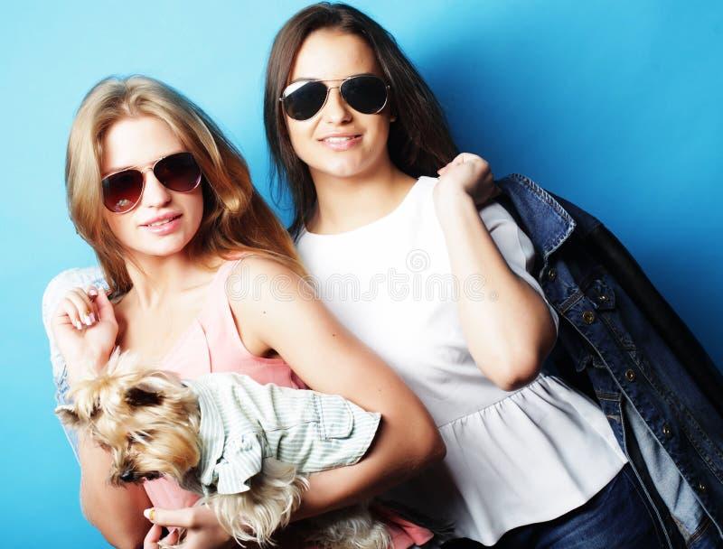 Livsstil och folkbegrepp: Två ung flickavänner som tillsammans står och rymmer hunden royaltyfri foto