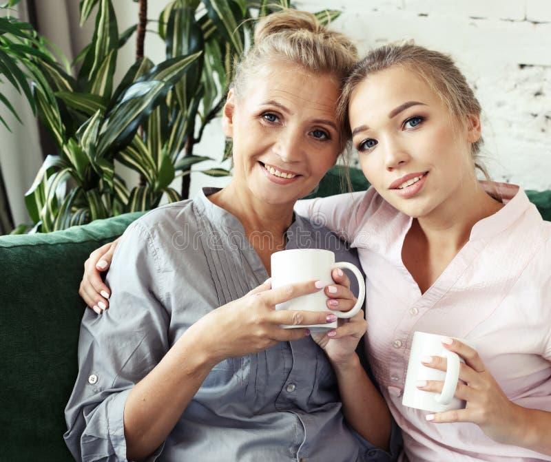 Livsstil och folkbegrepp: Tv? h?rliga kvinnor moder och dottersammantr?de p? soffan hemma arkivbild