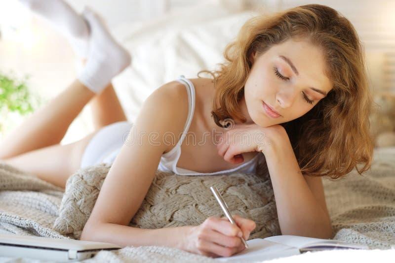 Livsstil och folkbegrepp: unga flickan skriver en dagbok medan ly arkivbilder