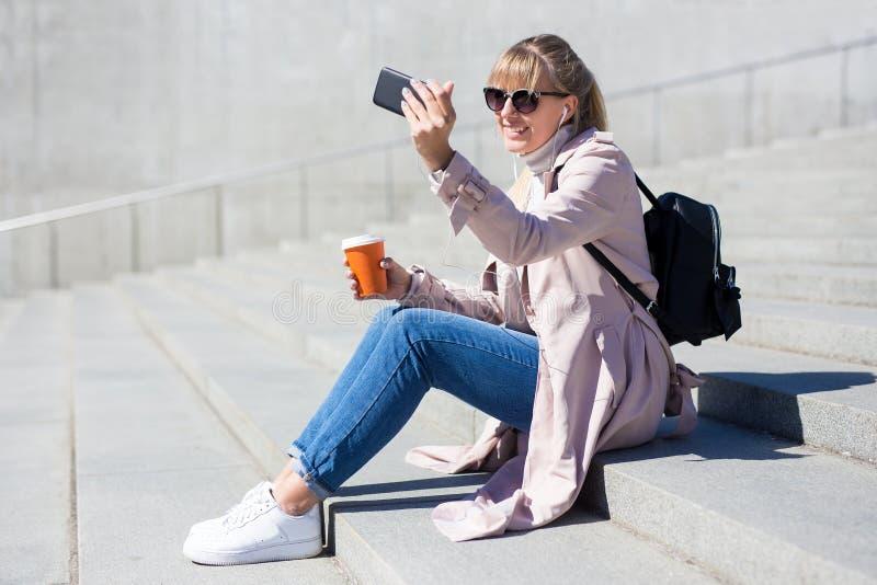 Livsstil och loppbegrepp - utomhus- stående av den unga kvinnan som sitter på trappa och tar selfiefotoet med smartphonen arkivfoton