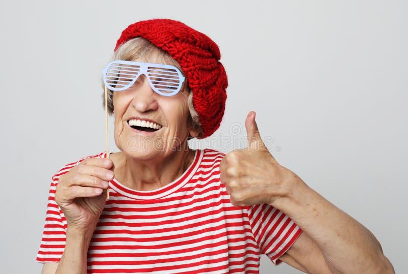 Livsstil, sinnesrörelse och folkbegrepp: den roliga farmodern med fejkar exponeringsglas, skratt och ordnar till för parti royaltyfri foto