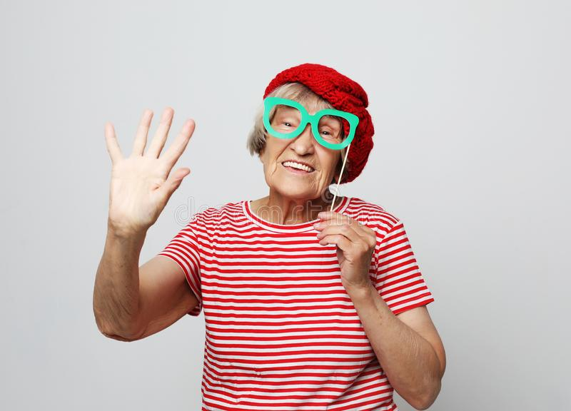 Livsstil, sinnesrörelse och folkbegrepp: den roliga farmodern med fejkar exponeringsglas, skratt och ordnar till för parti arkivbilder