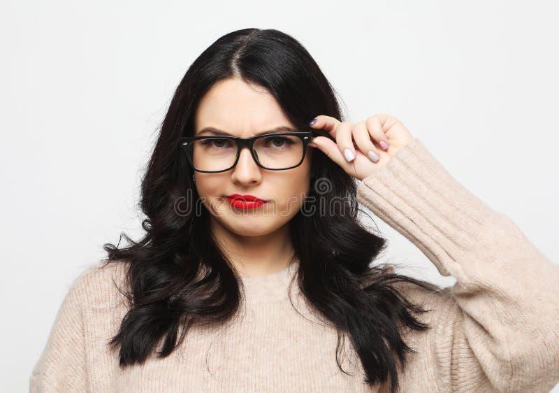 Livsstil, sinnesrörelse och folkbegrepp - den unga kvinnan som bär glasögon, ser incredulously och reflekterar arkivfoton