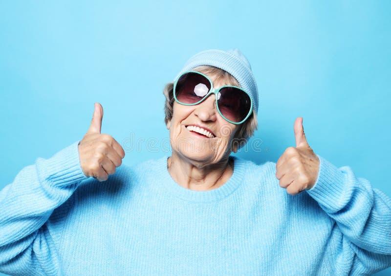 Livsstil, sinnesrörelse och folkbegrepp: Rolig gammal dam som bär den blåa tröjan, hatten och solglasögon som visar segertecknet arkivbild