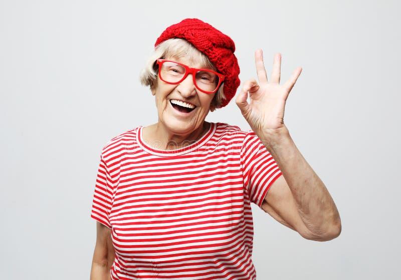 Livsstil, sinnesrörelse och folkbegrepp: Rolig gammal dam som bär den röda hatten och glasögon som visar det ok tecknet royaltyfri bild