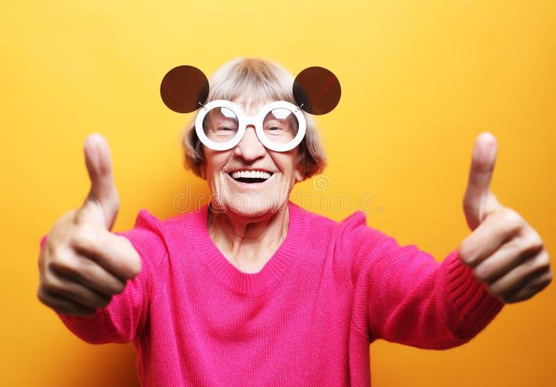 Livsstil, sinnesrörelse och folkbegrepp: Rolig gammal dam som bär den rosa tröjan och solglasögon som visar det ok tecknet royaltyfria bilder