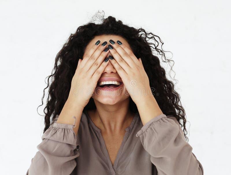 Livsstil, sinnesrörelse och folkbegrepp - ung kvinna som täcker hennes ögon med hennes händer över vit bakgrund arkivbild