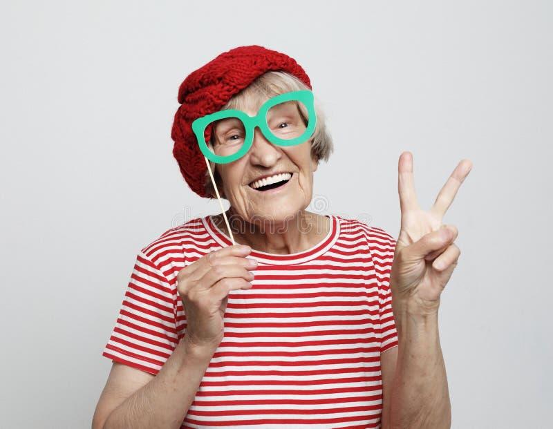 Livsstil, sinnesr?relse och folkbegrepp: den roliga farmodern med fejkar exponeringsglas, skratt och ordnar till f?r parti royaltyfria bilder