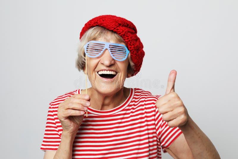 Livsstil, sinnesr?relse och folkbegrepp: den roliga farmodern med fejkar exponeringsglas, skratt och ordnar till f?r parti fotografering för bildbyråer