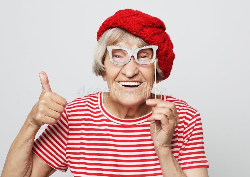 Livsstil, sinnesr?relse och folkbegrepp: den roliga farmodern med fejkar exponeringsglas, skratt och ordnar till f?r parti arkivbilder