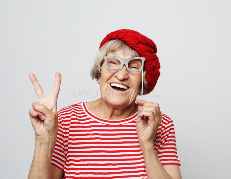 Livsstil, sinnesr?relse och folkbegrepp: den roliga farmodern med fejkar exponeringsglas, skratt och ordnar till f?r parti arkivfoton