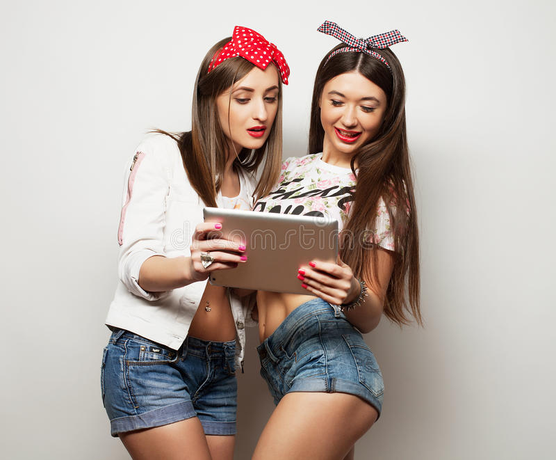 Livsstil-, tehnology- och folkbegrepp: Lyckliga flickor med minnestavladatoren över vit bakgrund royaltyfri bild