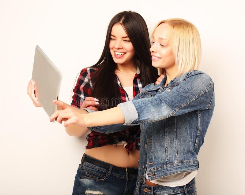 Livsstil-, tehnology- och folkbegrepp: Lyckliga flickor med tabellen royaltyfri foto