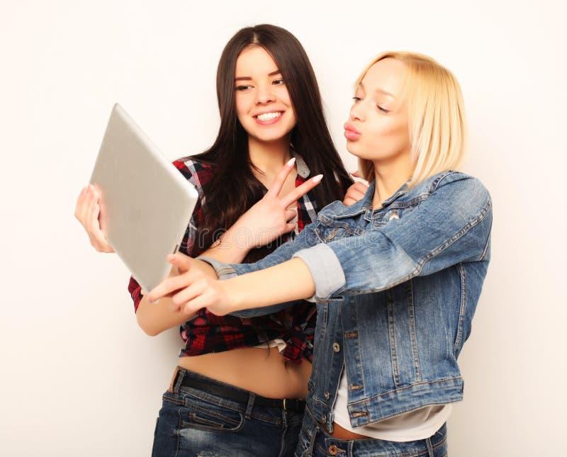 Livsstil-, tehnology- och folkbegrepp: Lyckliga flickor med tabellen royaltyfri fotografi
