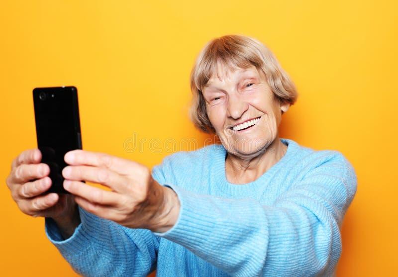Livsstil-, tehnology- och folkbegrepp: mormodern i blå tröja ler och tar en selfie royaltyfri foto