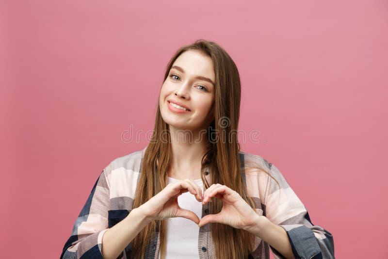 Livsstilbegrepp: Härlig attraktiv kvinna i den vita skjortan som gör ett hjärtasymbol med hennes händer royaltyfri bild