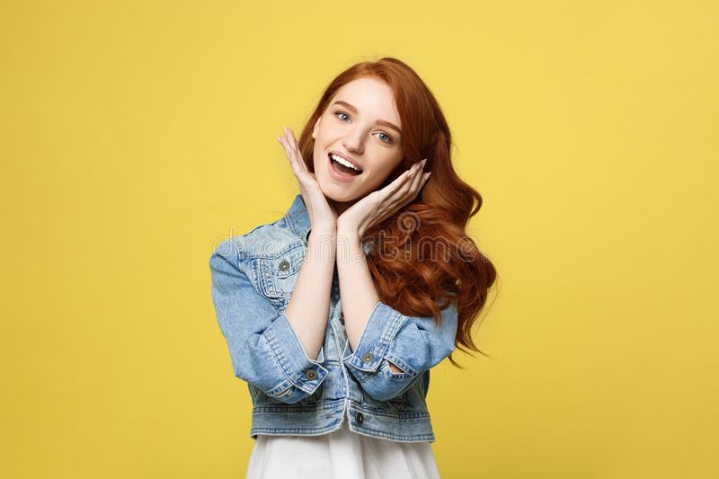 Livsstilbegrepp: Le den härliga unga kvinnan i jean beklär att posera med händer på hakan Isolerat över yellow royaltyfri fotografi