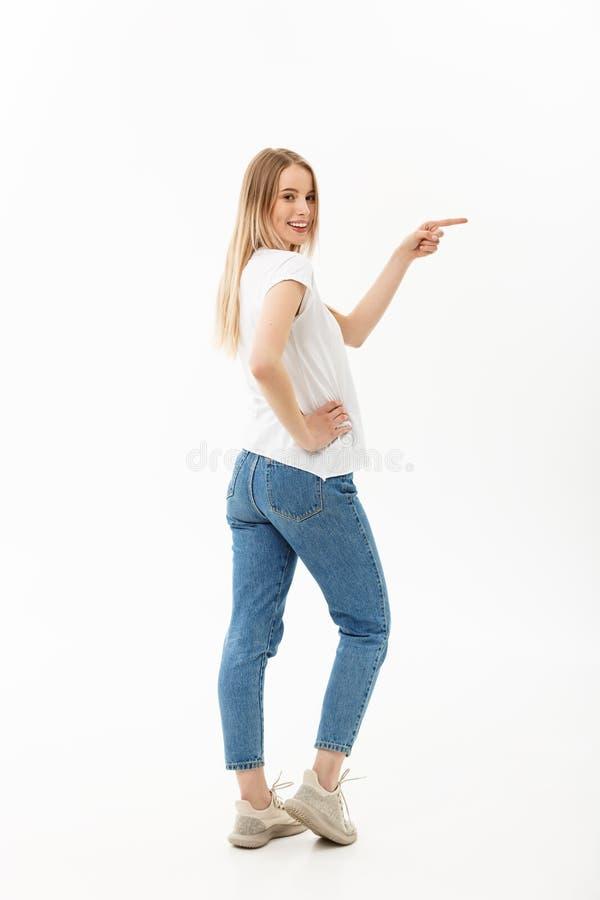 Livsstilbegrepp: Ståendekvinna som pekar eller skjuter något med pekfingret Isolerad härlig tillfällig ung kvinna arkivfoton
