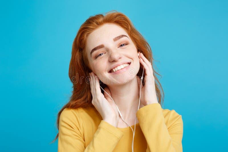 Livsstilbegrepp - ståenden av den gladlynta lyckliga ljust rödbrun röda hårflickan tycker om att lyssna till musik med glad hörlu royaltyfria bilder