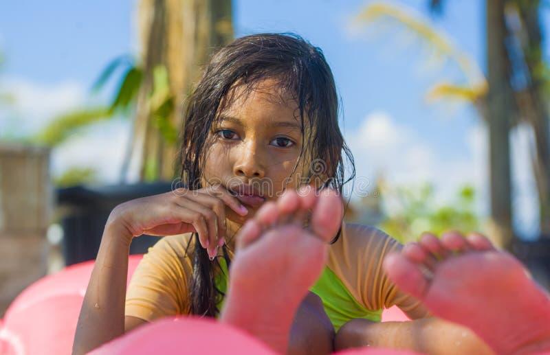 Livsstildet friastående av det unga söta och ursnygga kvinnliga barnet som har gyckel som ligger på uppblåsbar luftmadrass i feri royaltyfria bilder