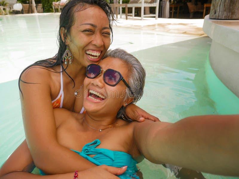 Livsstildet friast?ende av asiatiska flickv?nner som tycker om sommarferier p? den tropiska simbass?ngen f?r strandsemesterort so fotografering för bildbyråer