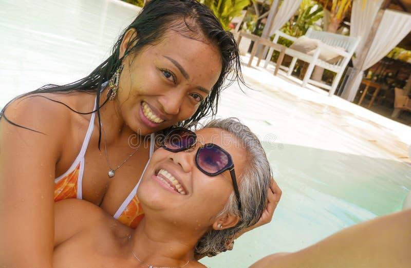 Livsstildet friast?ende av asiatiska flickv?nner som tycker om sommarferier p? den tropiska simbass?ngen f?r strandsemesterort so royaltyfri foto