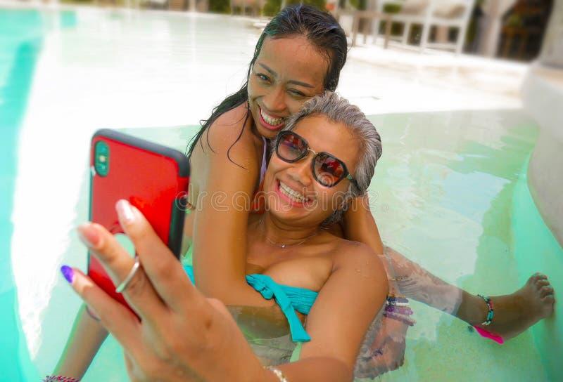 Livsstildet friast?ende av asiatiska flickv?nner som tycker om sommarferier p? den tropiska simbass?ngen f?r strandsemesterort so royaltyfria bilder