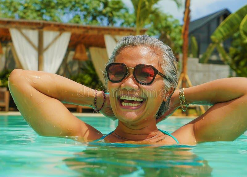 Livsstildet friast?enden av den lyckliga och attraktiva mogna asiatiska indonesiska kvinnan i bikini som tycker om tropiska ferie arkivfoto