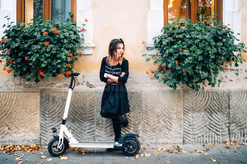 Livsstildetaljer, lycklig flicka med blommor i stads- stad som tycker om den elektriska sparkcykeln Lycka och bekymmerslöst begre royaltyfri foto