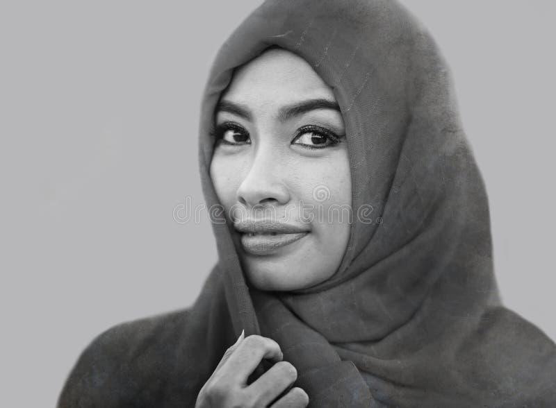 Livsstilen isolerade ståenden av ungt härligt och lyckligt asiatiskt le för kvinna som täcktes av halsduken för muslimhijabhuvude royaltyfri fotografi