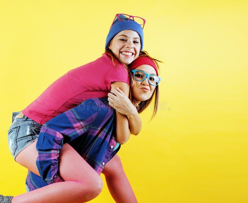 Livsstilfolkbegrepp: två nätta barn skolar tonårs- flickor som har roligt lyckligt le på gul bakgrund fotografering för bildbyråer
