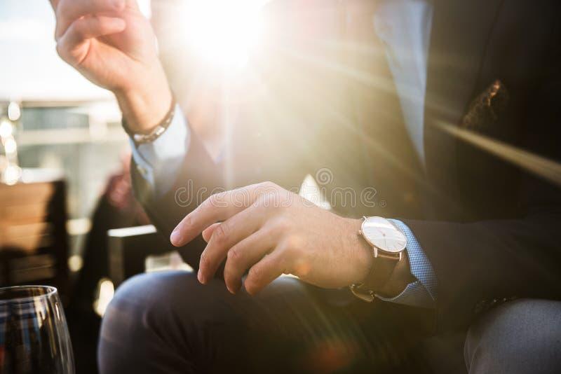 Livsstilfoto av eleganta affärsmän som bär den lyxiga klockan och har matställen i restaurang efter lyckad arbetsdags arkivfoton