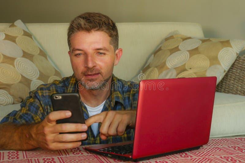 Livsstilhemstående av den unga hemmastadda soffasoffan för lycklig och attraktiv man som arbetar på bärbar datordatoren genom att royaltyfria foton