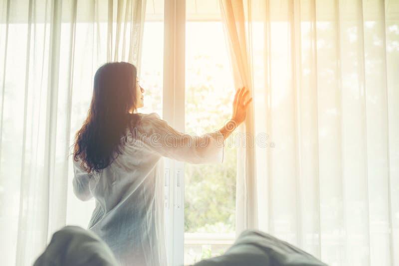 Livsstilkvinnor öppnar fönstret efter för att få upp den vita sängen i morgonsoluppgång koppla av lynne i sovrummet royaltyfria bilder
