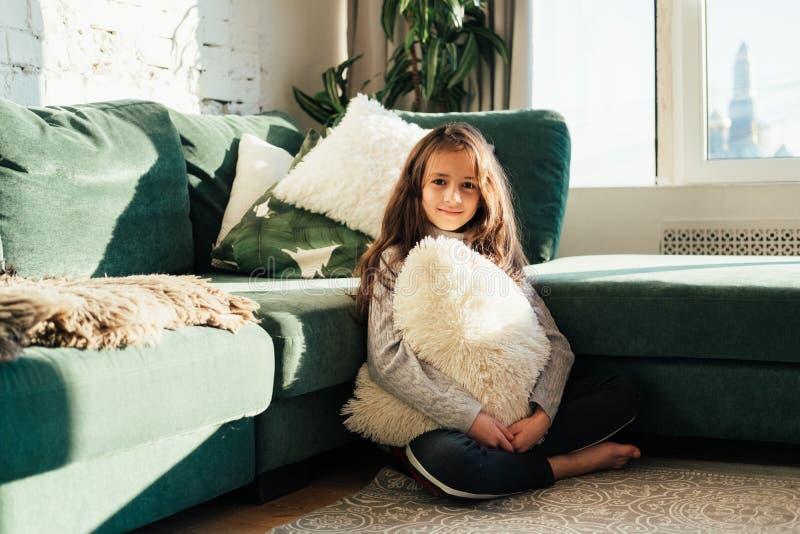 Livsstilmodeståenden av den unga stilfulla hipsterbarnflickan som sitter nära soffan, den bärande gulliga moderiktiga dräkten som arkivfoto